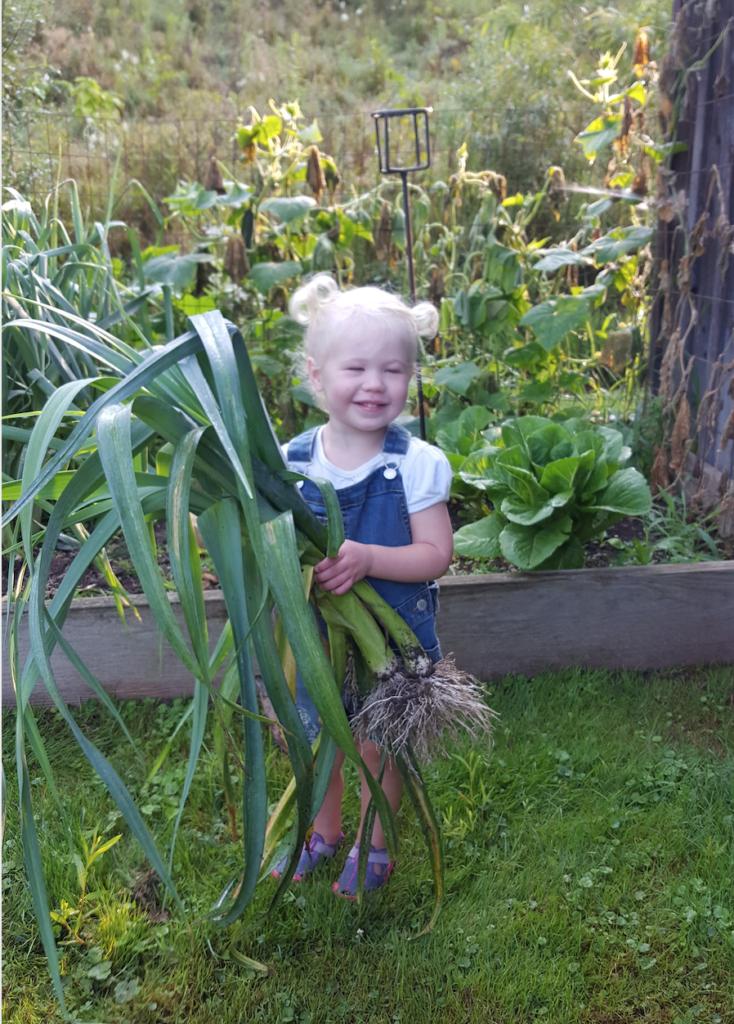 little girl holding leeks